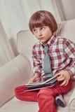 Skolpojke som bär en rutig skjorta som hemma sitter på en soffa med uppsättningen av minnestavlor arkivbild