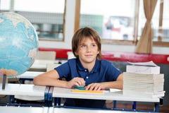 Skolpojke som bort ser med jordklotet och böcker på Royaltyfri Foto