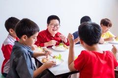 Skolpojke som ler, medan ha lunch med vännen fotografering för bildbyråer