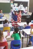 Skolpojke som rymmer en amerikanska flaggan i klassrum arkivfoton