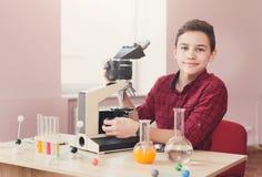 Skolpojke som ser i mikroskop på kurs arkivfoto