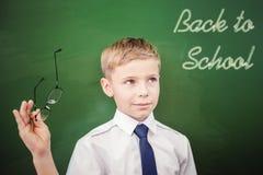 Skolpojke som ser till svart tavla med text av tillbaka till skolan Royaltyfria Foton