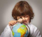 Skolpojke som studerar jordklotet Arkivbilder
