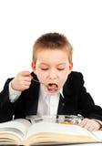 Skolpojken äter i klassrumet fotografering för bildbyråer
