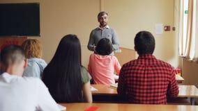 Skolpojken lyfter handen och svarande fråga för lärare` s, medan utbildaren kontrollerar kunskap som framme står av stock video