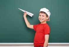 Skolpojken med pappersnivålek nära en svart tavla, tömmer utrymme, utbildningsbegrepp Arkivbilder