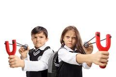 Skolpojken och en skolflicka som siktar med katapulter och, vaggar arkivfoton