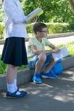Skolpojken reflekterad med en bok i hans händer, en flicka läser en bok på en utomhus- kurs arkivbild