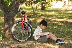 Skolpojken sitter på jordningen i en äpplefruktträdgård eller skog arkivfoton