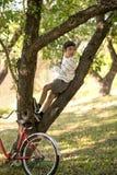 Skolpojken sitter på trädet i äppleträdgård eller skog honom loen fotografering för bildbyråer