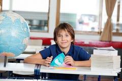 Skolpojkesammanträde med böcker och jordklotet på skrivbordet Royaltyfri Bild