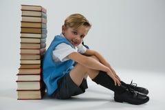 Skolpojkesammanträde mot bokbunt på vit bakgrund Fotografering för Bildbyråer