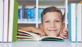 Skolpojkesammanträde på tabellen och läseboken i arkiv Arkivfoton