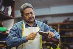 Skomakare som reparerar en sko arkivfoton