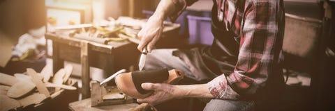 Skomakare som rymmer en kniv och en sko royaltyfri foto