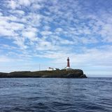 The Skomvær lighthouse between the sky and the sea. royalty free stock image
