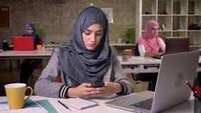 Skoncentrowana ładna muzułmańska dziewczyna w hijab siedzi przy miejsce pracy i używa jej telefon komórkowego blisko jej laptopu