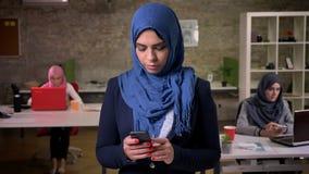Skoncentrowana środkowa wschodnia kobieta w błękitnym hijab pisać na maszynie na jej telefonie i patrzeje w dół podczas gdy stoją