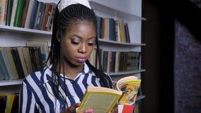 Skoncentrowana afrykańska żeńska pozycja w bibliotecznej i czytelniczej książce z interesem