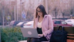 Skoncentrowana atrakcyjna kobieta używa laptop w parku podczas gdy siedzący na ławce zbiory wideo