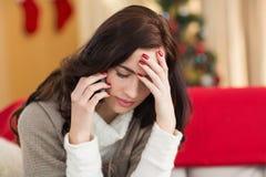 Skoncentrowana brunetka na telefonie na święto bożęgo narodzenia Zdjęcie Royalty Free