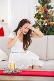 Skoncentrowana brunetka na telefonie na święto bożęgo narodzenia Obrazy Royalty Free