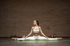 Skoncentrowana dama rozszczepia nogi oddzielnie i rozciąga na joga macie zdjęcia royalty free