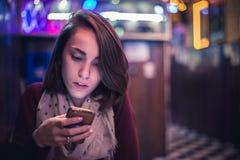Skoncentrowana dziewczyna patrzeje twój telefon komórkowy w barze fotografia stock