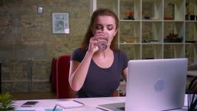 Skoncentrowana imbirowa caucasian kobieta pisać na maszynie na laptopie i trinking woter w breakes podczas gdy siedzący spokojnie