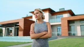 Skoncentrowana kobieta stoi blisko luksusu domu Poważnej kobiety relaksująca pobliska willa zbiory wideo