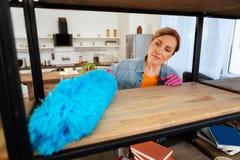 Skoncentrowana kobieta używa błękitnego luksusowego panicle podczas gdy walczący z pyłem fotografia royalty free
