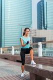 Skoncentrowana młoda żeńska atleta robi skoku krokowi podnosi ćwiczenie na ławce na miasto ulicie zdjęcie royalty free