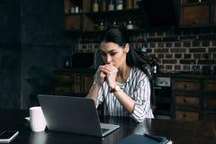 skoncentrowana młoda kobieta patrzeje laptopu ekran podczas gdy siedzący obraz royalty free