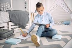Skoncentrowana medytacyjna chłopiec próbuje online uczenie Fotografia Stock