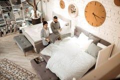 Skoncentrowana para obserwuje łóżko i poduszki proponować w kompleksie zdjęcie stock