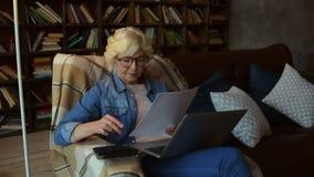 Skoncentrowana starsza kobieta robi jej pieniężnemu planowaniu zbiory wideo