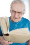 Skoncentrowana starszego mężczyzna czytelnicza książka w domu obraz royalty free