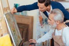 Skoncentrowanego artysty starszych osob pomaga mężczyzna w obrazie fotografia stock