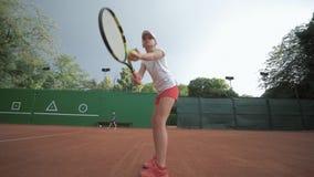 Skoncentrowanego i poważnego gracza w tenisa dziewczyny ciupnięcia nastoletni kant na piłce przy fachowym czerwień sądem podczas  zbiory