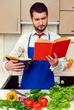 Skoncentrowanego młodego człowieka czytelnicza książka kucharska Fotografia Stock