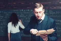 Skoncentrowanego profesora czytelniczy artyku? klasa podczas gdy m?ody ?e?ski ucze? pisze na pok?adzie obraz royalty free