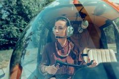 Skoncentrowanej atrakcyjnej kobiety pilotowy jest ubranym potrzebny wyposa?enie obraz royalty free