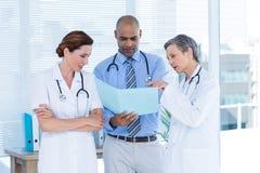Skoncentrowani medyczni koledzy analizuje kartotekę wpólnie Zdjęcie Stock