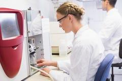 Skoncentrowani naukowowie pracuje z medyczną maszyną Fotografia Stock