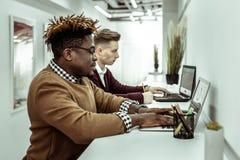 Skoncentrowani ruchliwie faceci pracuje z ich laptopami podczas gdy siedzący wpólnie fotografia royalty free