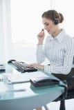 Skoncentrowany żeński faktorski obsiadanie przy jej biurkiem jest ubranym słuchawki obrazy royalty free