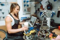 Skoncentrowany żeński mechanik ma odpoczynek w remontowym sklepie zdjęcie royalty free