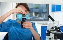 Skoncentrowany żeński naukowiec w mundurze otwiera szklanego słój dla c obrazy stock