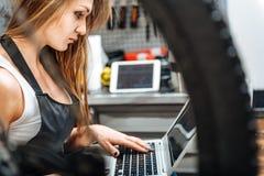Skoncentrowany żeński technik używa gadżet w warsztacie zdjęcia stock
