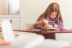 Skoncentrowany żeński uczeń absorbedly czyta Obrazy Stock
